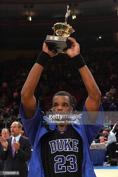 Shelden Williams of the Duke University Blue Devils raises the player of the game trophy following Dukes win over the Memphis University Tigers in...