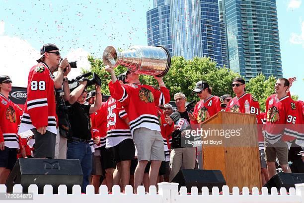 Sheldon Brookbank, defenseman for the Chicago Blackhawks, raises and kisses the Stanley Cup Trophy during the Chicago Blackhawks' 2013 Stanley Cup...