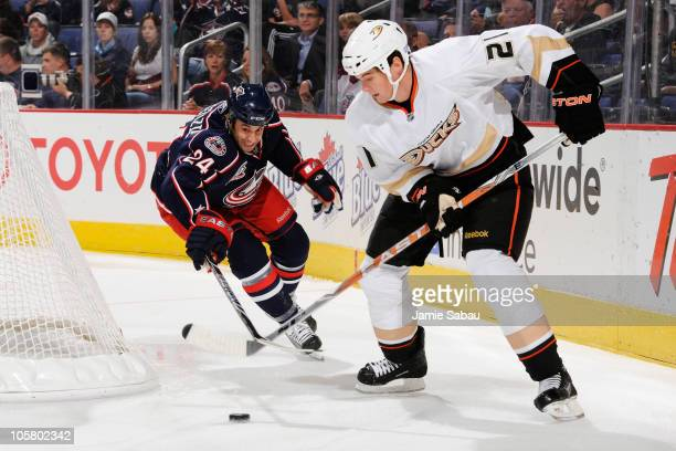 Sheldon Brookbank of the Anaheim Ducks attempts to keep control of the puck away Derek MacKenzie of the Columbus Blue Jackets during the first period...