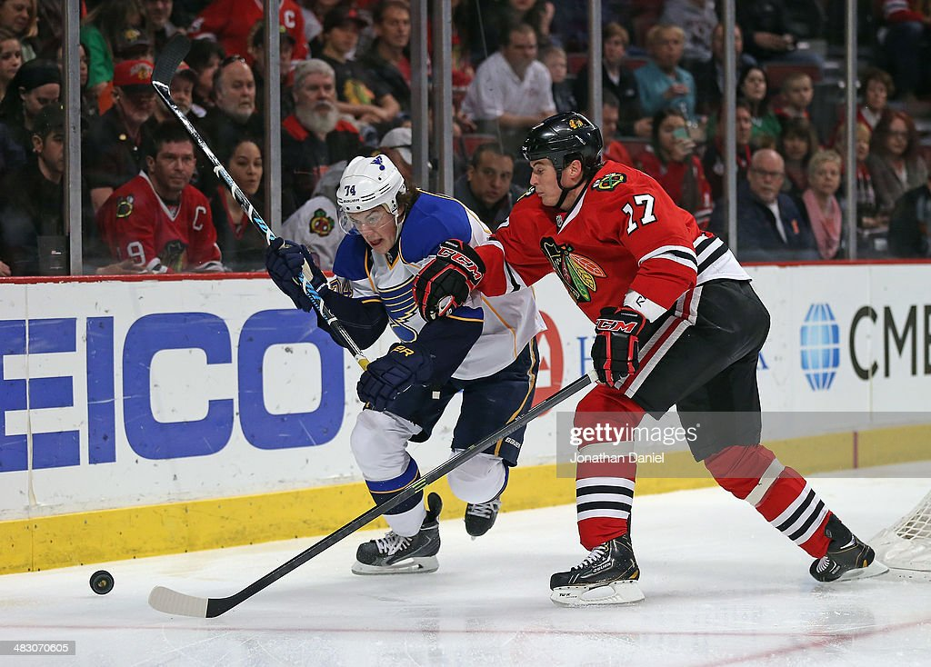 Sheldon Brookbank #17 of the Chicago Blackhawks and T.J. Oshie #74 of the St. Louis Blues move to the puck at the United Center on April 6, 2014 in Chicago, Illinois.