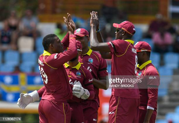 Sheldon Cottrell and Jason Holder of West Indies celebrate the dismissal of Jonny Bairstow of England during the 5th and final ODI between West...