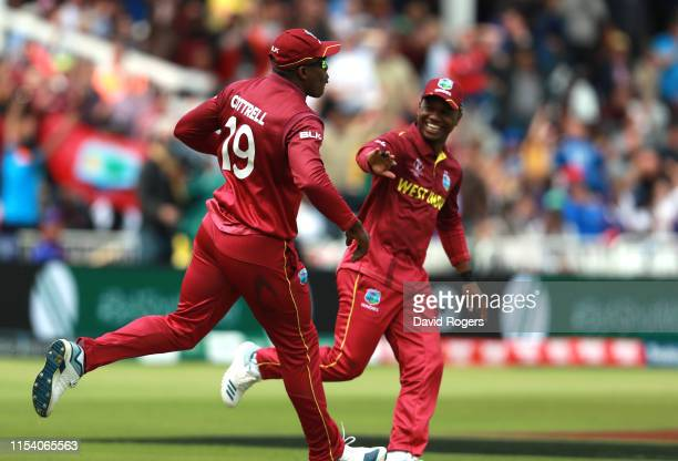Sheldon Cottrell of the West Indies celebrates with team mate Evin Lewis after catching out Steve Smith during the Group Stage match of the ICC...