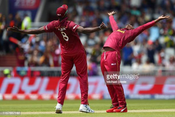 Sheldon Cottrell of West Indies celebrates alongside captain Jason Holder after taking the wicket of Colin Munro of New Zealand during the Group...