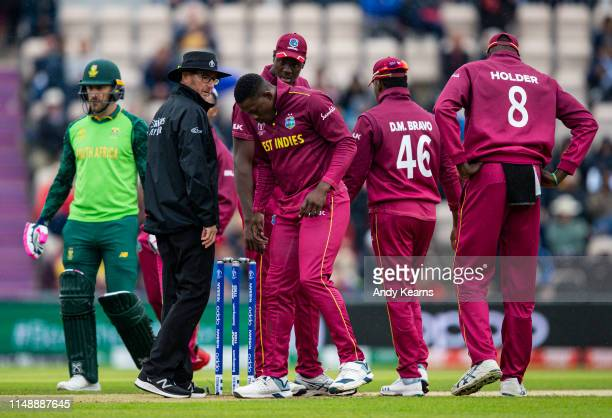 Sheldon Cottrell of West Indies shows concern about the wet condition of the bowlers run up area during the Group Stage match of the ICC Cricket...