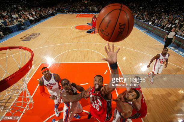 Sheldon Williams of the New Jersey Nets shoots against Amar'e Stoudemire and Tyson Chandler of the New York Knicks during a preseason game against on...