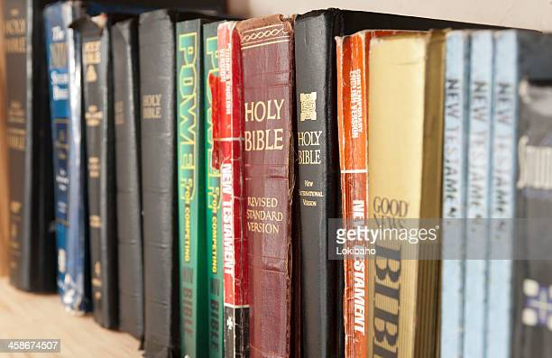 shelf full of bible translations - religious text stock pictures, royalty-free photos & images