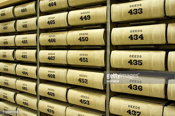 a shelf full of numbered deeds - deed stock photos and pictures