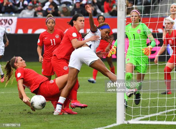 Shelina Zadorsky and Christine Sinclair of Canada defend Jessica McDonald of the United States as she goes for a shot on goal off a corner kick in...