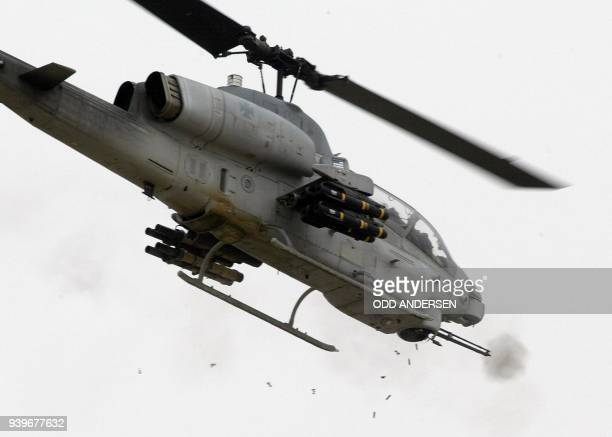 Shell casing drops to the ground as a US AH1W Super Cobra helicopter fires on positions in the strategic southern port of Umm Qasr 22 March 2003 US...