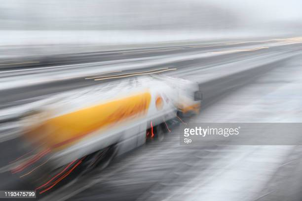 shell fuel deliviry truck driving on a highway during a snow blizzard - shell brand name stock pictures, royalty-free photos & images