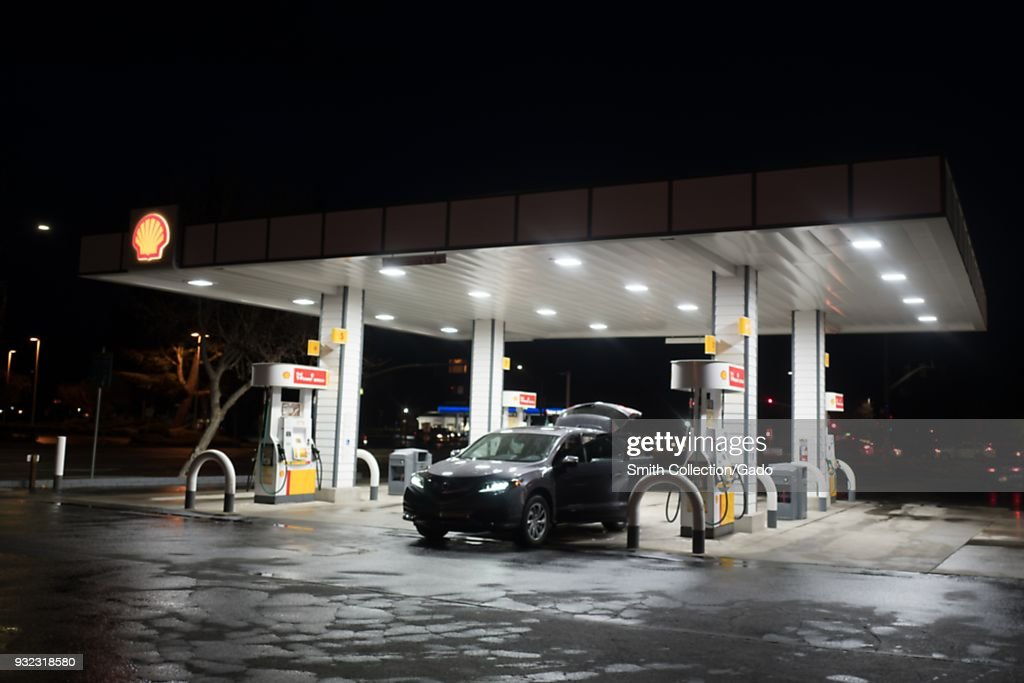 A Shell gas station is brightly illuminated at night as a car fills