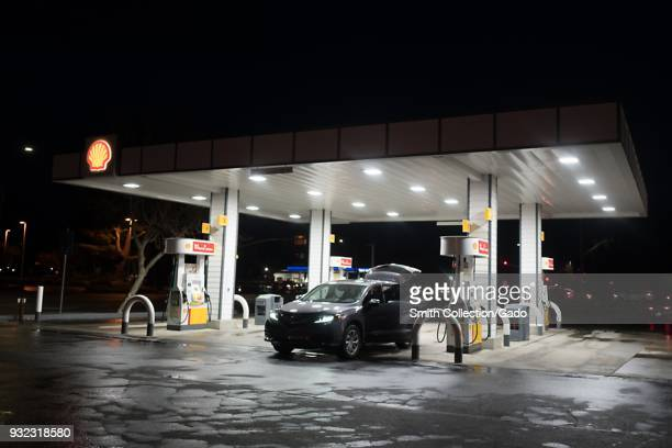 A Shell gas station is brightly illuminated at night as a car fills up with fuel in Dublin California March 12 2018