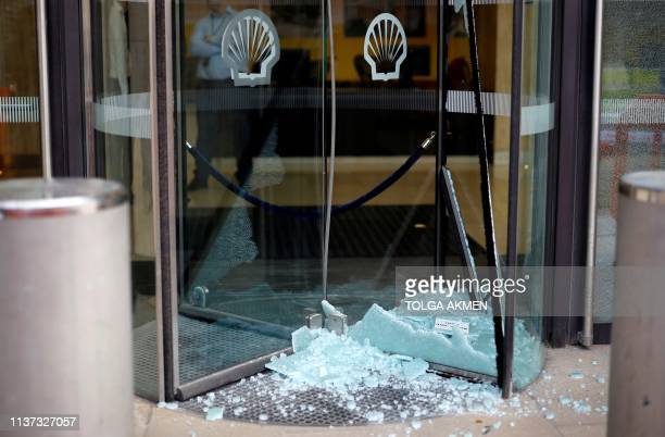 Shell logos are pictured above brokedn glass on the damaged door of the Shell Centre in London, the UK offices of Royal Dutch Shell, during an...