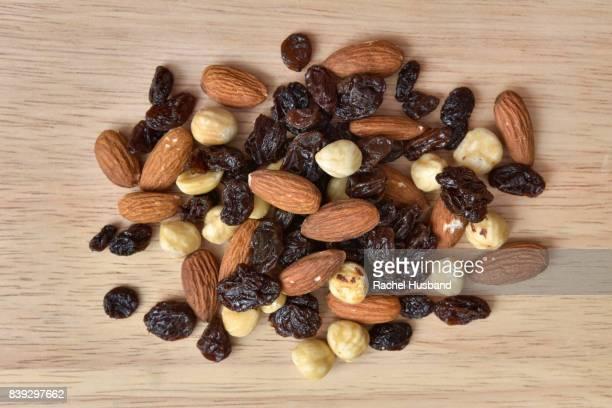 Shelled almonds, shelled hazelnuts and raisins on chopping board