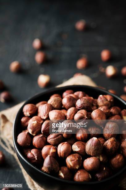 shelled hazelnuts on black - brycia james stock pictures, royalty-free photos & images