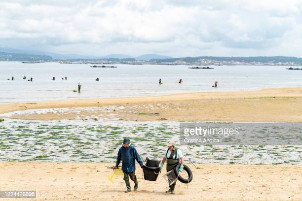 Shellfishermen leave the beach after picking up clams on May 12 2020 in A Pobra do Caramiñal Spain The shellfishermen of A Pobra do Caramiñal...