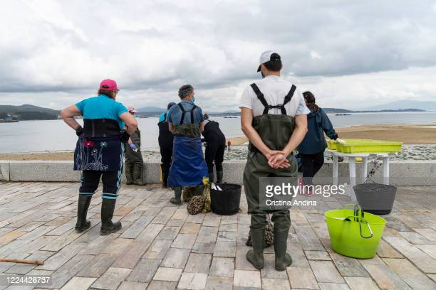 Shellfishermen line up to weigh the clams they've collected on May 12 2020 in A Pobra do Caramiñal Spain The shellfishermen of A Pobra do Caramiñal...