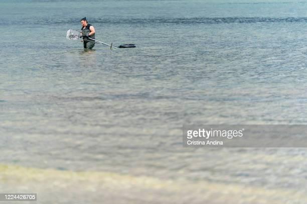 Shellfisherwoman picking up clams in the Ría de Arousaon May 12, 2020 in A Pobra do Caramiñal, Spain.The shellfishermen of A Pobra do Caramiñal...
