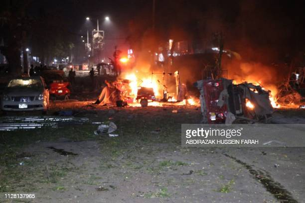 Shells of vehicles burn outside the Maka AlMukarama hotel in the Somalia capital Mogadishu on February 28 2019 after a car bomb exploded killing at...