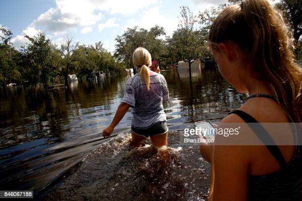 Shelly Hughes and her daughter Kylie Hughes make their way through their flooded campground to check on their camper at the Peace River Campground in...