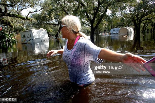 Shelly Hughes hands her cell phone back to her daughter so she can go deeper into the water as the pair make their way through their flooded...