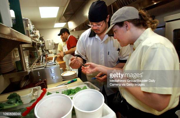 Shelly Wallingford, right, an inspector for the Boulder County Public Health Department, watches Dave Hillman , kitchen manager at the Le Peep...