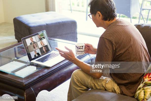 covid-19 shelter in place and social distancing in effect, businessman working with virtual business group through live streaming, video conferencing virtual office - hot desking stock pictures, royalty-free photos & images
