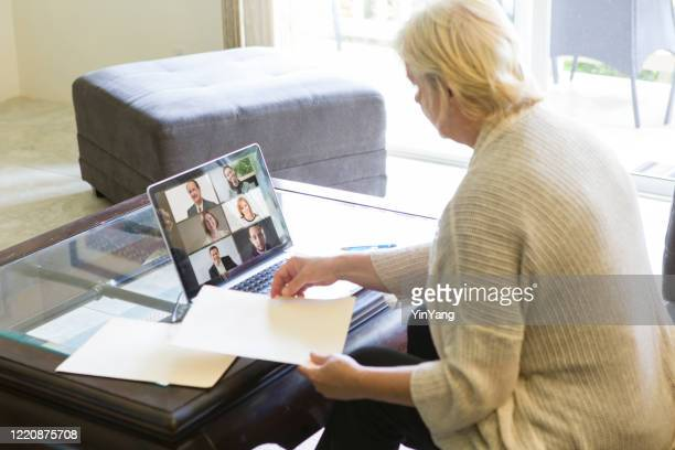 covid-19 shelter in place and social distancing in effect, businesswoman working with virtual business group through live streaming, video conferencing virtual office - remote location stock pictures, royalty-free photos & images