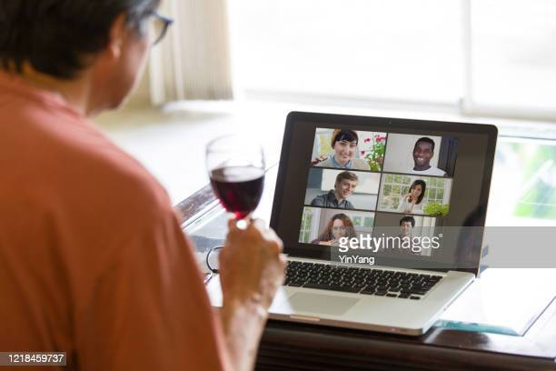 covid-19 shelter in place and social distancing in effect, virtual social life continue through live streaming, video conferencing virtual gathering - happy hour stock pictures, royalty-free photos & images