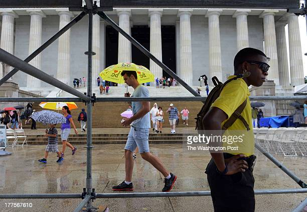 WASHINGTON DC AUGUST Sheltered from the rain under a media riser a man stands guard as crews work to prepare the scene for the coming 50th...