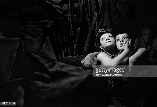 Sheltering from a heavy mortar bombardment 67 year old Antonia Arapovic hugs her neighbour's terrified child in the darkness of a underground cellar...