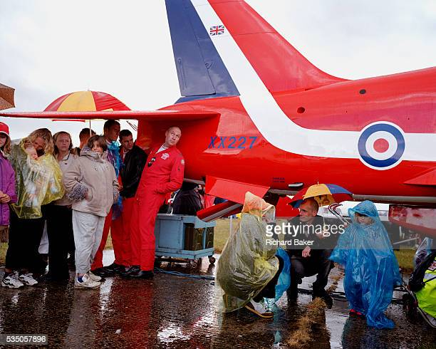Sheltering from a rain shower at the Kemble Air Day some pilots of the elite 'Red Arrows' Britain's prestigious Royal Air Force aerobatic team gather...