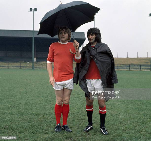 Sheltering from the weather, Manchester United footballer George Best with actor Hywel Bennett during the filming of 'Percy' at the Cliff training...