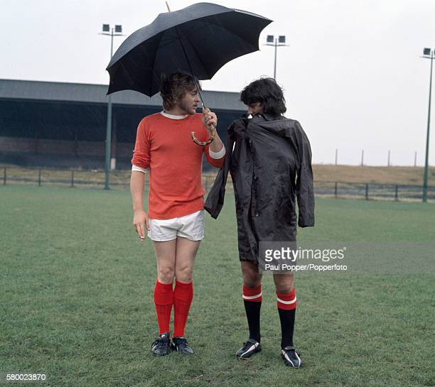 Sheltering from the weather Manchester United footballer George Best with actor Hywel Bennett during the filming of 'Percy' at the Cliff training...