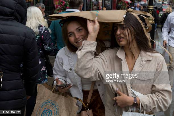 Sheltering under a shopping bag two women hurry through London's streets during unseasonal June showers on 15th June 2019 in London England
