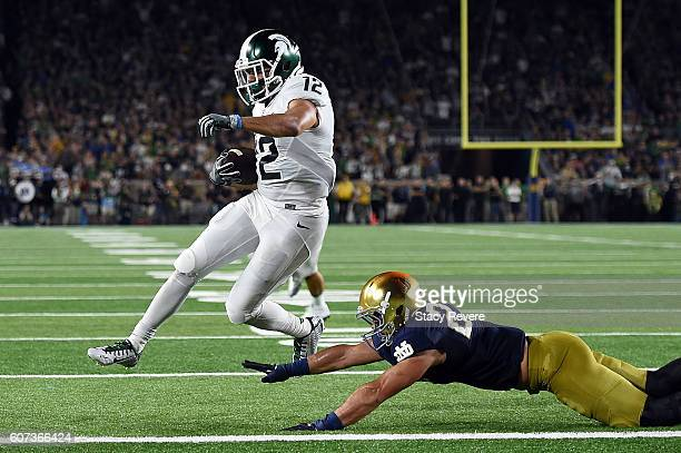J Shelton of the Michigan State Spartans scores a touchdown in front of Drue Tranquill of the Notre Dame Fighting Irish during the first half of a...