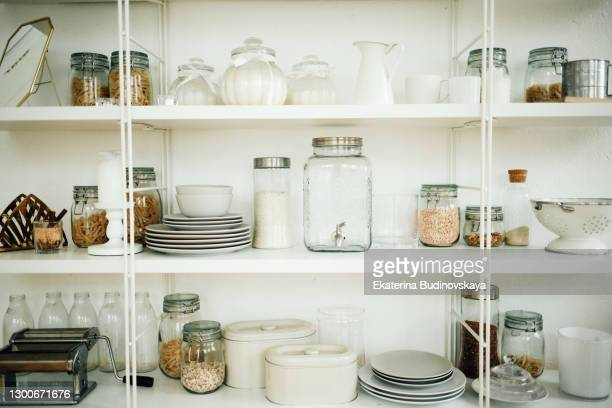 shelves in the kitchen with dishes and spices - キャビネット ストックフォトと画像