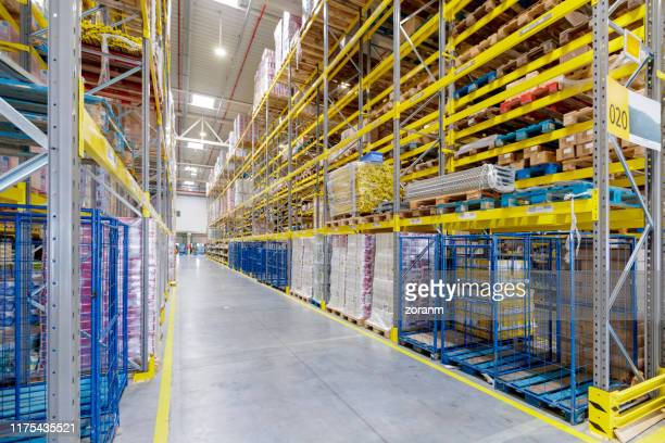 shelves lined with boxes in distribution warehouse - industrial storage bins stock pictures, royalty-free photos & images