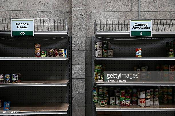Shelves of canned foods sit partially empty at the SFMarin Food Bank on May 1 2014 in San Francisco California Food banks are bracing for higher food...