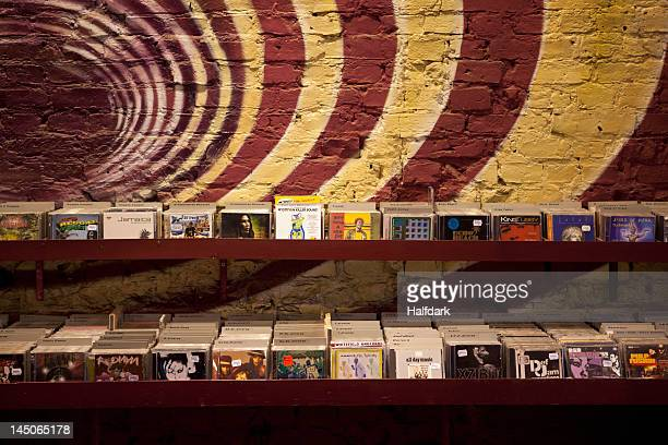 shelves of compact discs in a record shop - compact disc stock pictures, royalty-free photos & images