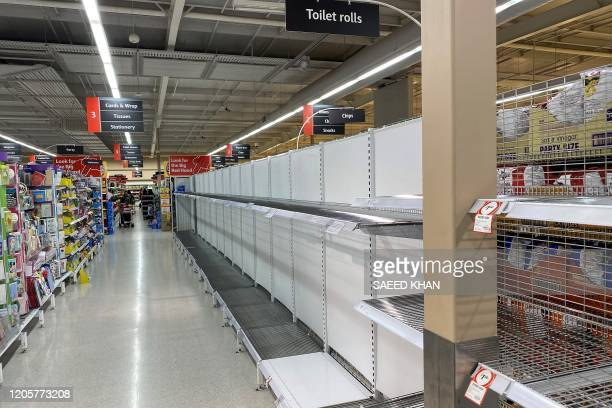 Shelves usually stocked with toilet rolls are seen empty in a supermarket following panic buying in Sydney on March 8, 2020. - A fight over toilet...