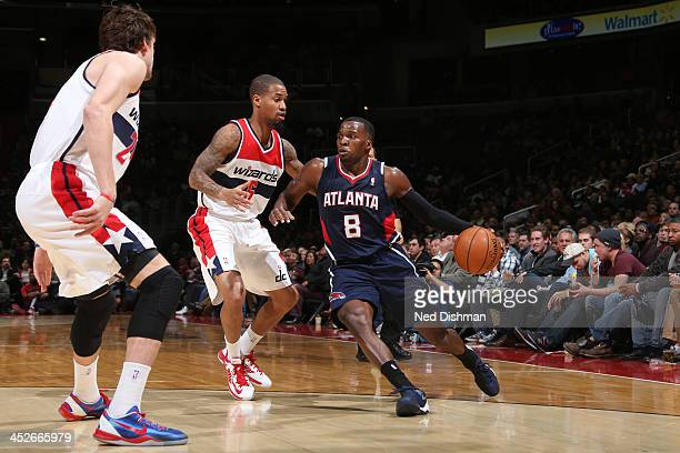 Shelvin Mack of the Atlanta Hawks drives against Eric Maynor and Jan Vesely of the Washington Wizards during the game at the Verizon Center on...