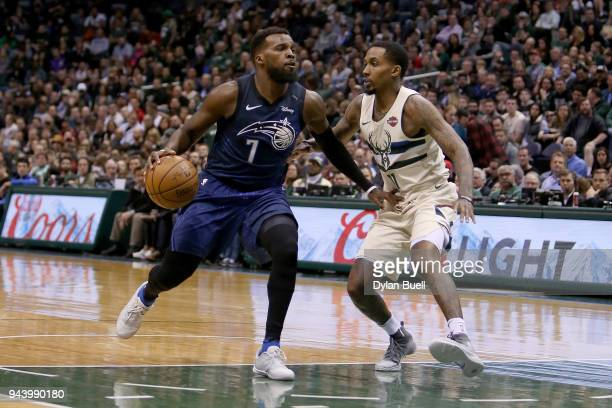 Shelvin Mack of the Orlando Magic dribbles the ball while being guarded by Brandon Jennings of the Milwaukee Bucks in the fourth quarter at the...