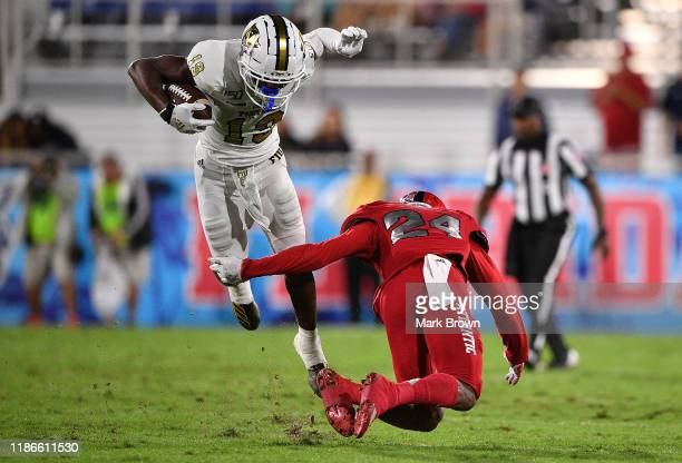 Shemar Thornton of the FIU Golden Panthers tries to avoid Zyon Gilbert of the Florida Atlantic Owls in the first quarter at FAU Stadium on November...
