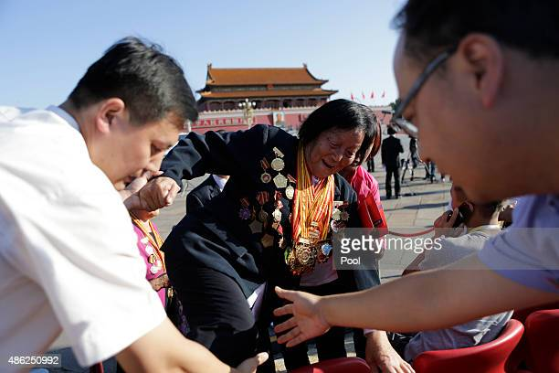 Shen Jilan wearing insignias and medals is helped to her seat ahead of the military parade to mark the 70th Anniversary of the end of World War Two...