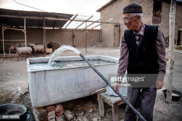 A shepherd fills a water tank he uses for his animals in the village of Lyaily near Beshkent Kyrgyzstan The local drinking water is vulnerable to...