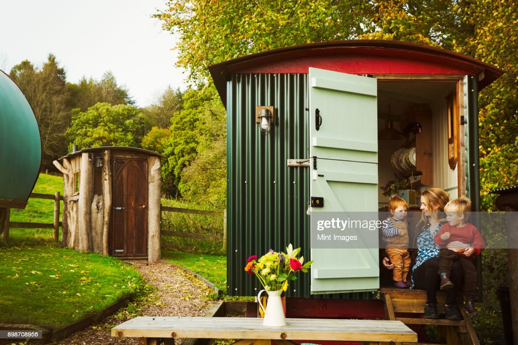 A shepherds hut with open door beside a path to a small rustic shed, and a woman with two small children seated on the step. : Stock Photo