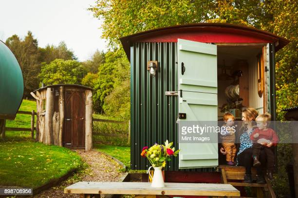 a shepherds hut with open door beside a path to a small rustic shed, and a woman with two small children seated on the step. - hut stock pictures, royalty-free photos & images