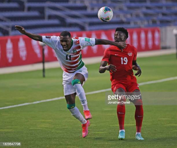 Sheraldo Becker of Suriname and Alphonso Davies of Canada battle for the ball during a FIFA World Cup Qualifier at SeatGeek Stadium on June 08, 2021...