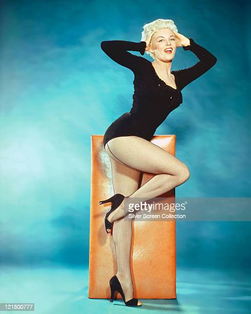 Sheree North US actress singer and dancer wearing a black longsleeved leotard with fishnet stockings poses standing on one leg with her other leg...